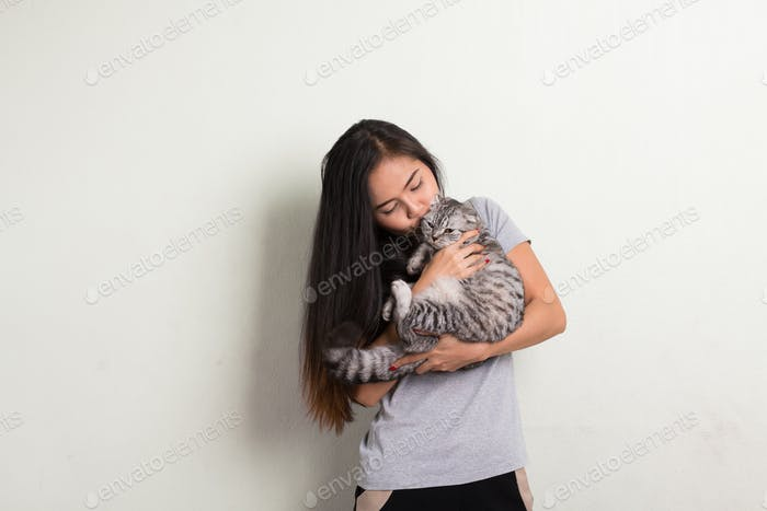 Young happy beautiful Asian woman kissing cute cat