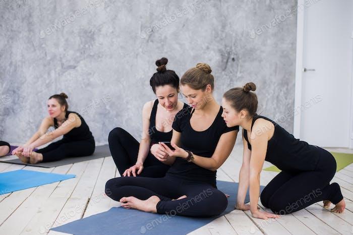 Niedlich Mädchen sitzen und Geselligkeit mit der Gruppe nach ihrer Yoga-Klasse