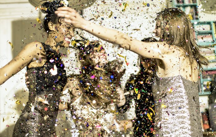 Group of young women celebrating at a party in a haze of falling glitter confetti.