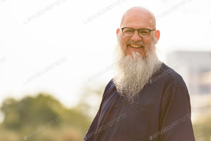 Portrait of happy mature bald bearded man with eyeglasses smiling