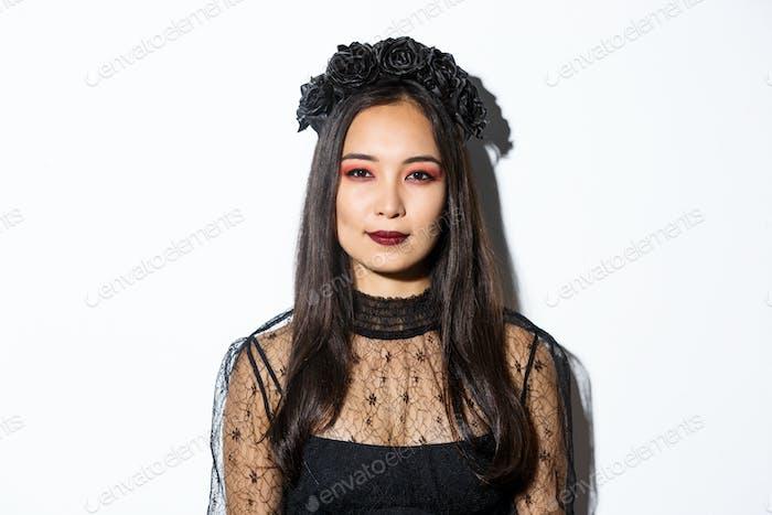 Nahaufnahme von schönen gotischen Mädchen mit schwarzem Kranz, immer angezogen für Halloween-Party, stehend