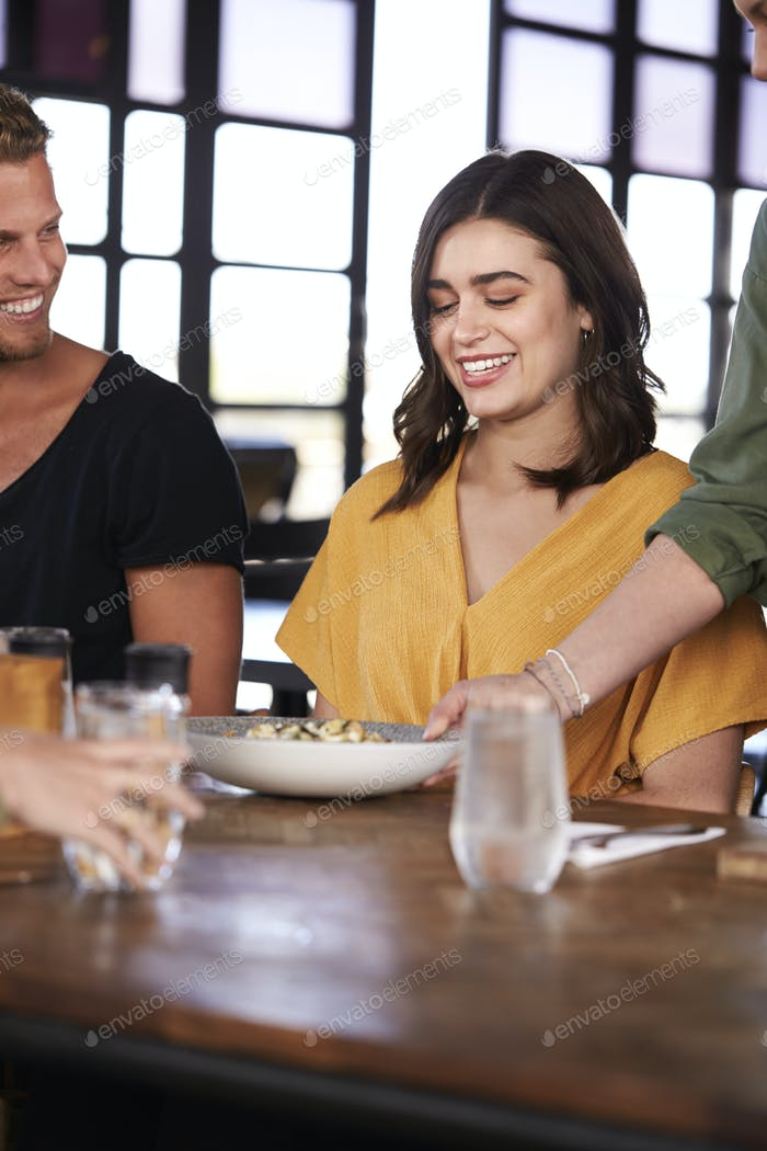 Waitress Serving Couple Meeting For Drinks And Food In Restaurant