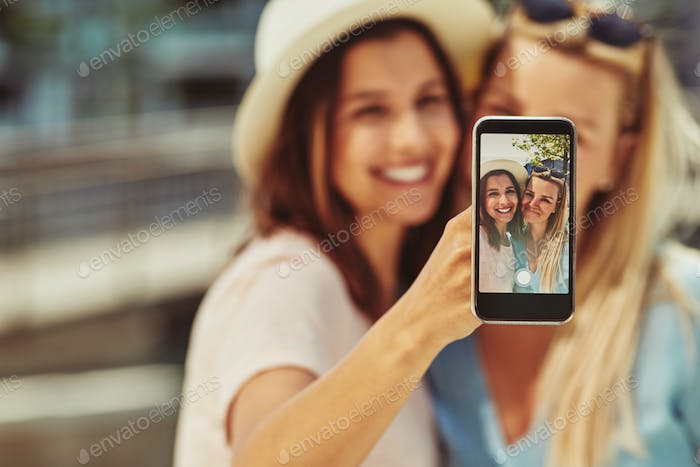 Thumbnail for Two young female friends taking selfies together outside in summer
