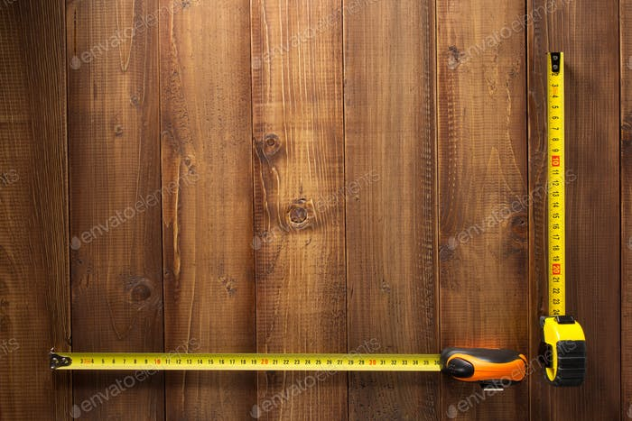 tape measure tools on wooden  background