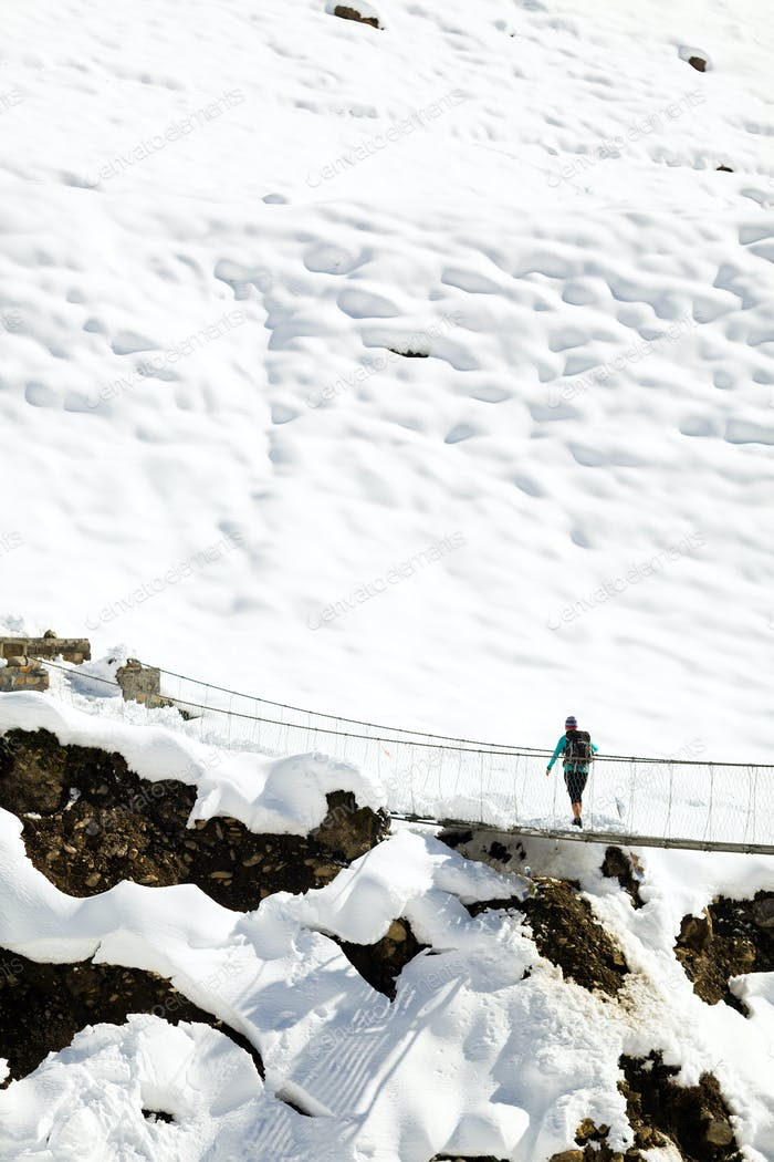 Woman walking on bridge in winter mountains