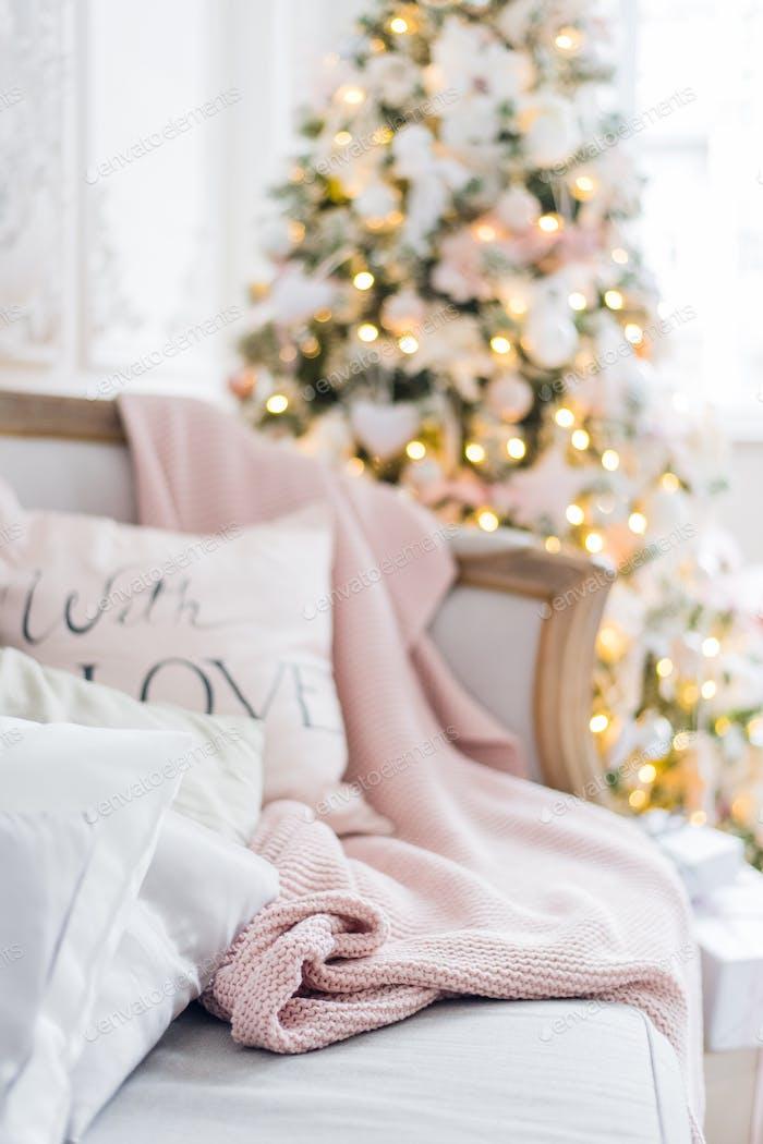 Cuadros de punto y almohadas en un sofá en Página de inicio en una víspera de Navidad. Comodidad en el Página de inicio