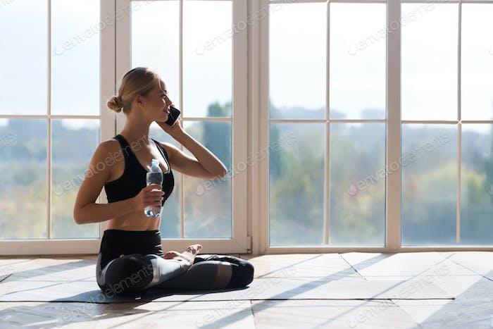 Yoga Mädchen trinken Wasser und reden mit dem Smartphone während der Pause
