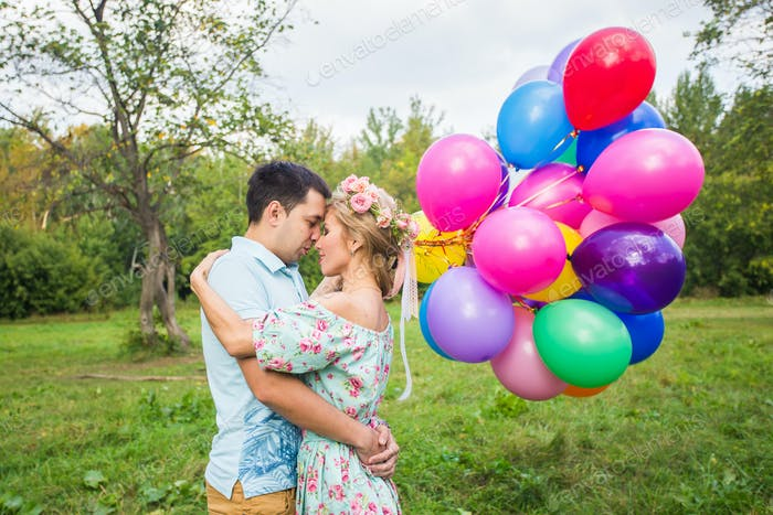 Young couple having weekend and walking with balloons on nature