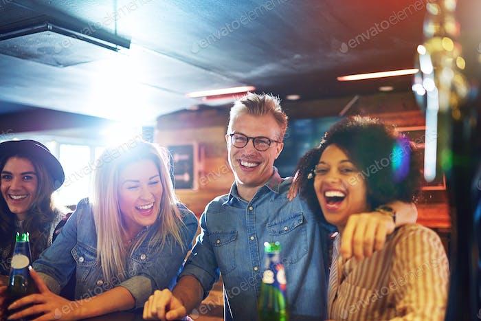 Lachende Freunde mit Bier an der Theke