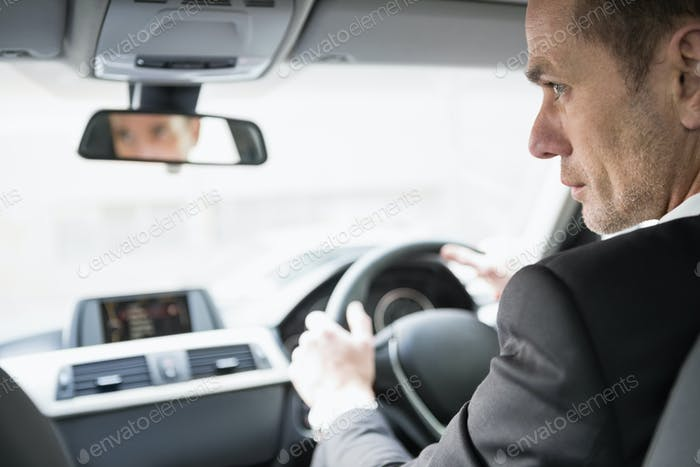 Businessman in the drivers seat in his car