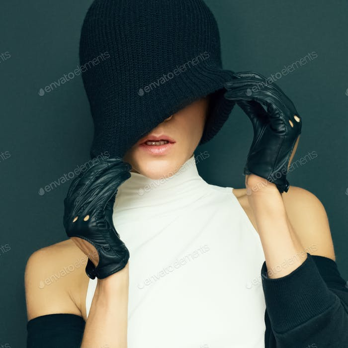 glamor model on black background in trendy gloves and hat autumn