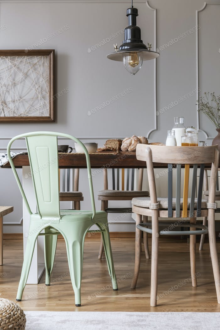 Chairs at wooden table under lamp in bright dining room interior