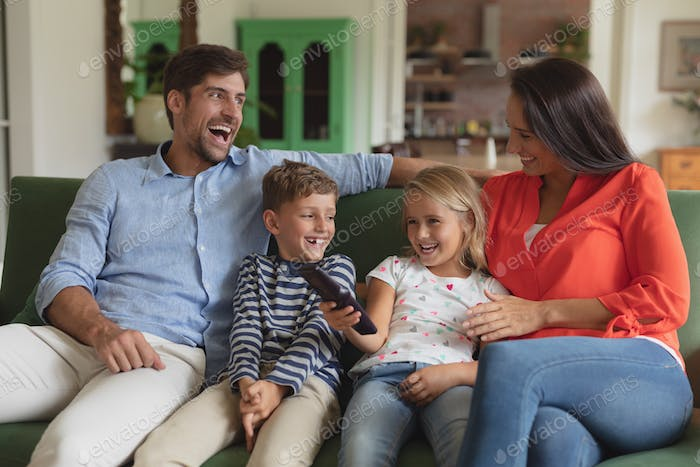 Front view of happy Caucasian family watching television in living room at home