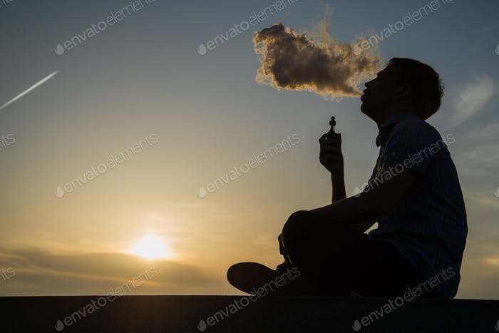 vaping young man with, produces vapor on sunset sky background at the sea coast promenade, place for
