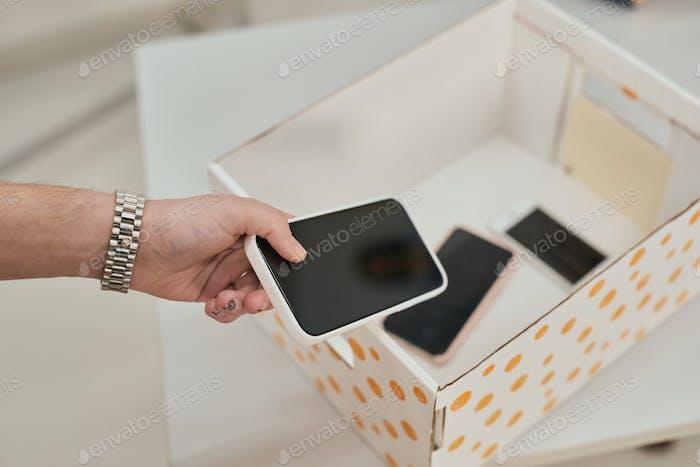 Man putting phone in box