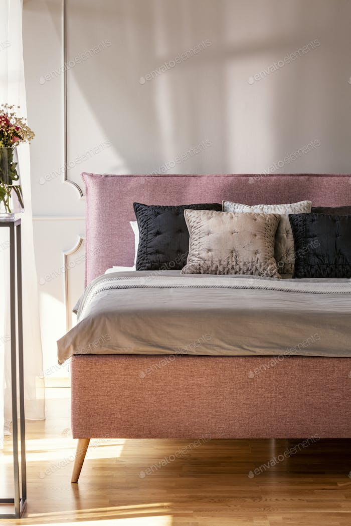 Pillows on bed in grey and pink bedroom interior with flowers an