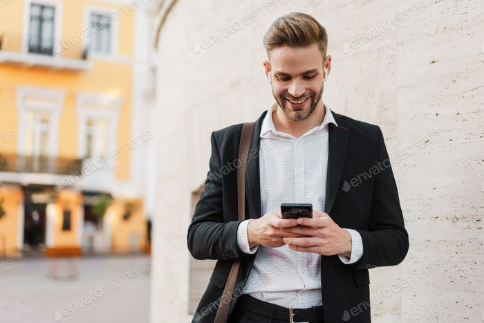 Handsome joyful businessman using wireless earphones and mobile phone