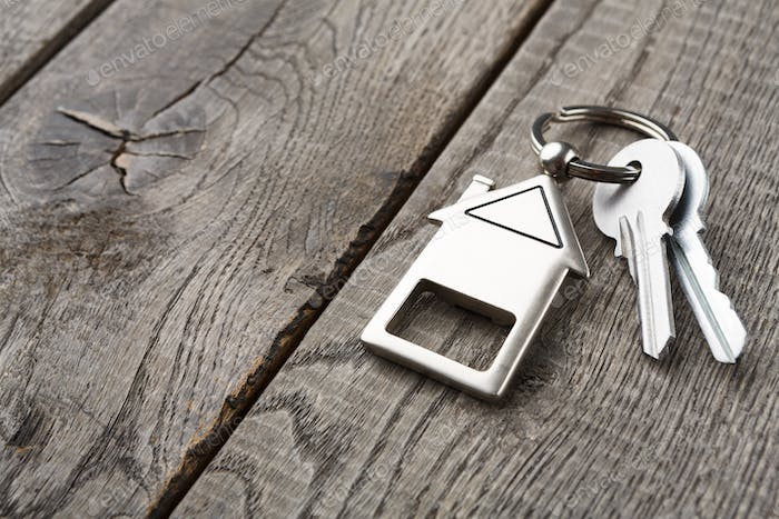 Bunch of keys with house shaped keychain on rustic wood
