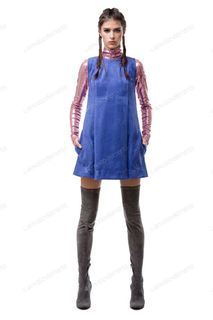 Beautiful young lady standing in blue suede dress and pink top with sequins and knee high boots