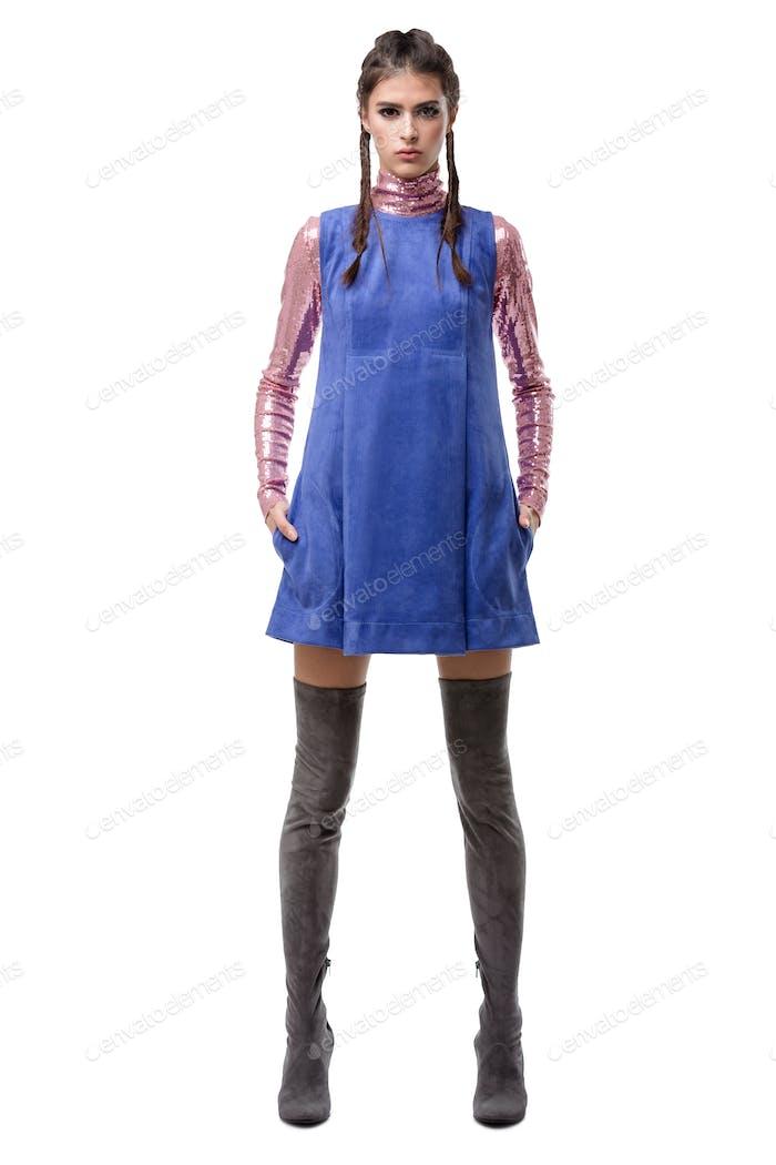 Schöne junge Dame stehend in blauem Wildlederkleid und rosa Top mit Pailletten und kniehohen Stiefeln