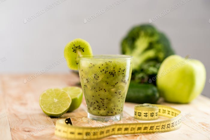 fresh fruit smoothie in glass with piece of kiwi, limes and measuring tape on tabletop
