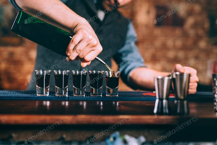 Close up details of bartender serving alcoholic drinks at party