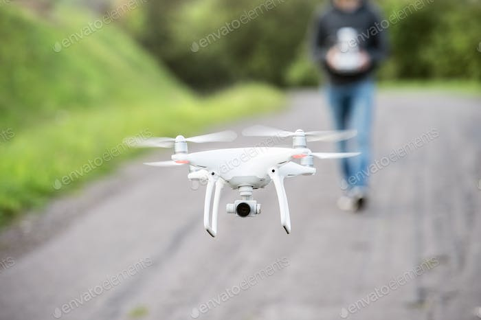 Unrecognizable man with flying drone. Sunny green nature.