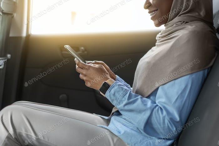 Mobile Communication. Black Businesswoman In Hijab Using Smartphone On Backseat Of Car