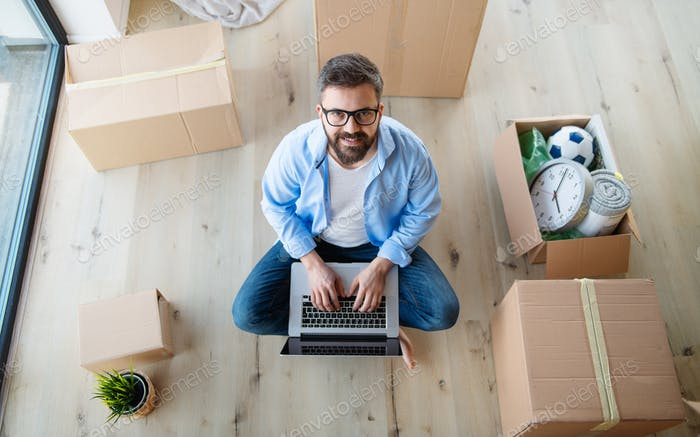 Top view of mature man with boxes moving in new house, using laptop.