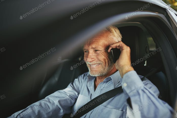 Smiling senior man driving his car talking on a cellphone