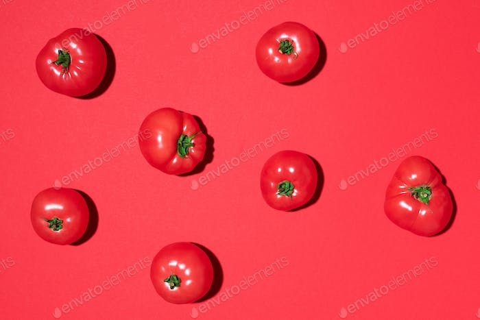 Red tomatoes pattern on red background. Flat lay, top view. Summer minimal concept. Vegan and