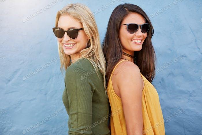 Zwei Frauen lächelnd zurück an Rücken