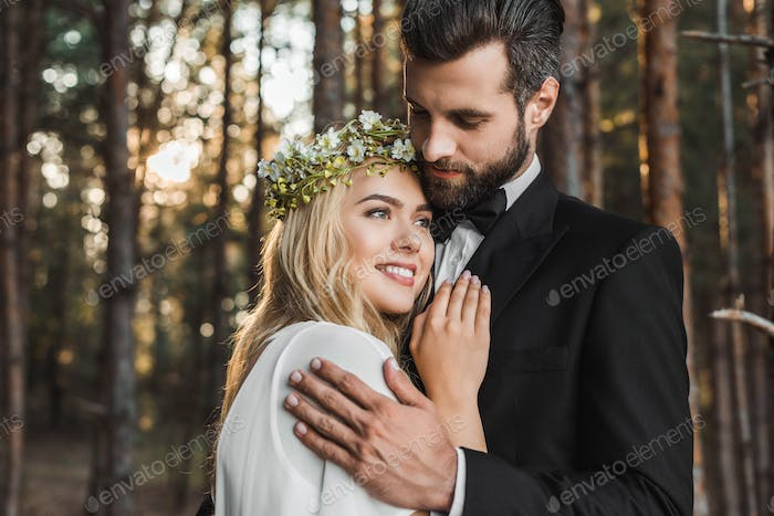 beautiful wedding couple hugging in forest
