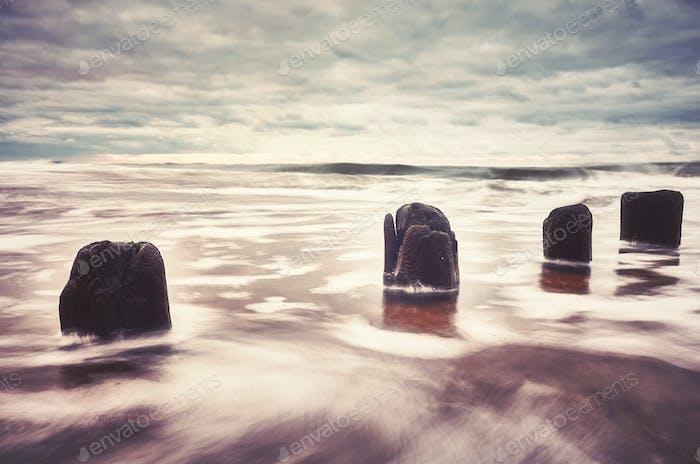 Farbgetöntes Bild von einem leeren Strand mit verschwommenem Wasser.