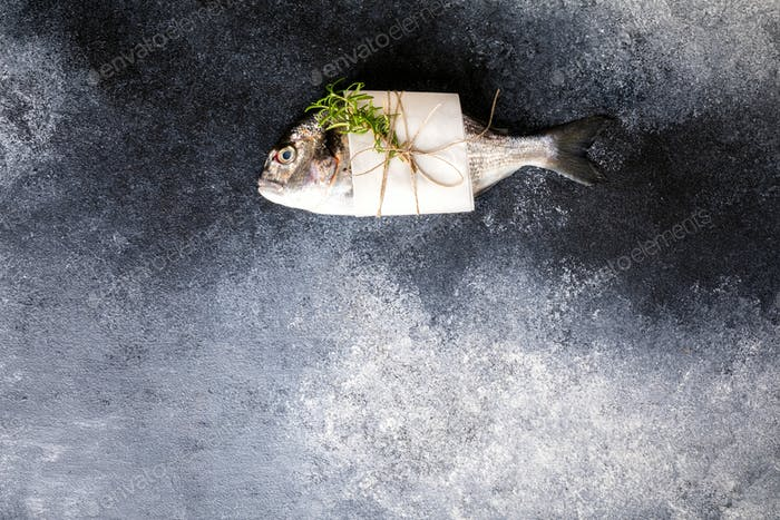 Fresh uncooked Dorado or sea bream fish with the ingredients