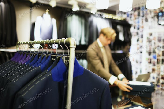 Close-up of suit rack at clothing store with designer working in background