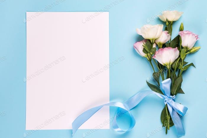 Eustoma Blumen mit Papierbogen auf blauem Hintergrund, Draufsicht. Valentinstag, Geburtstag, Mutter oder