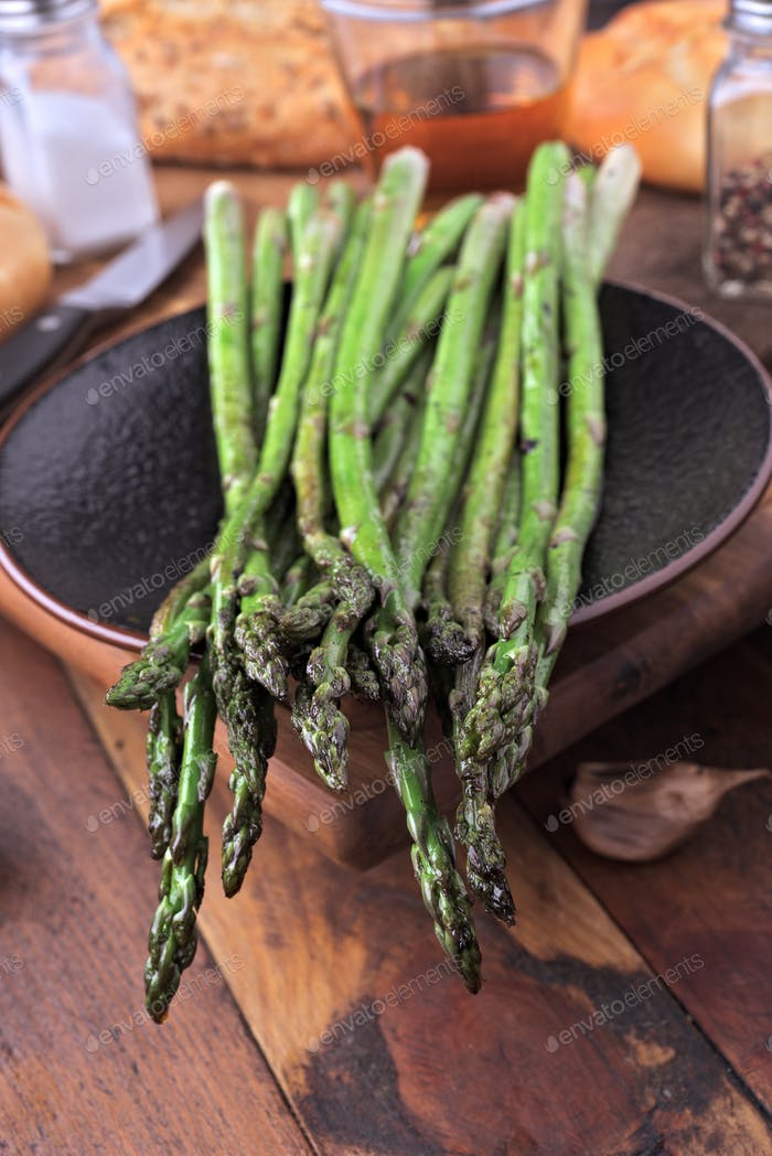 bunch of cooked green asparagus on classic wooden board