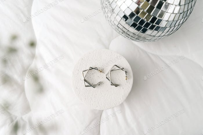 Silberne moderne Bijouterie-Ohrringe auf weißem Hintergrund.