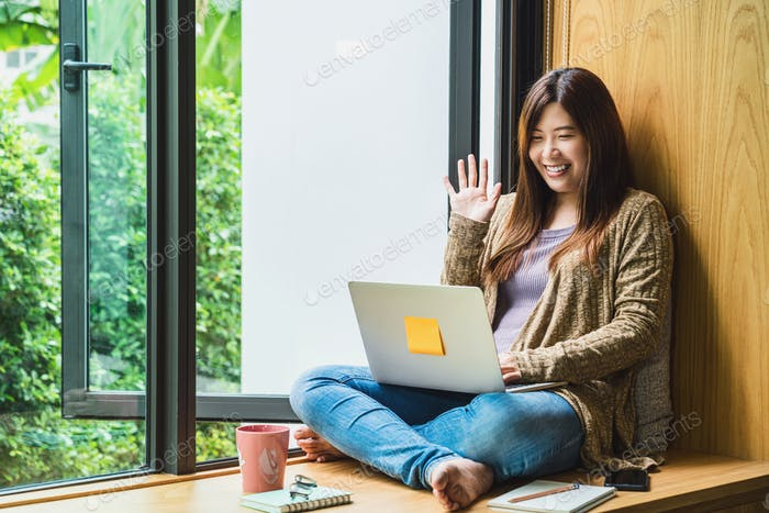 Asian business woman using technology laptop and working from home with say hello or bye