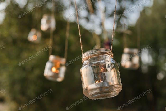 Mason jar candle hanging on tree for wedding decor