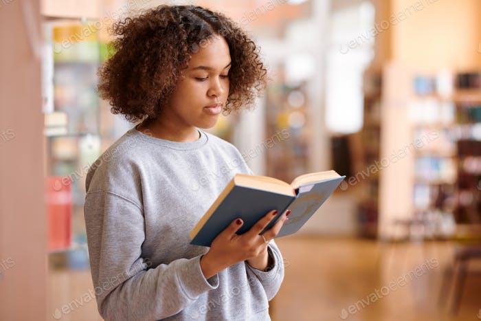 Wavy-haired multicultural girl in grey sweatshirt reading book of tales
