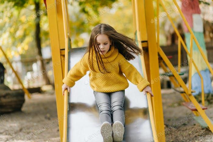 Chica  preadolescente caucásica jugando al aire libre. Niño en suéter amarillo frío en el patio de recreo