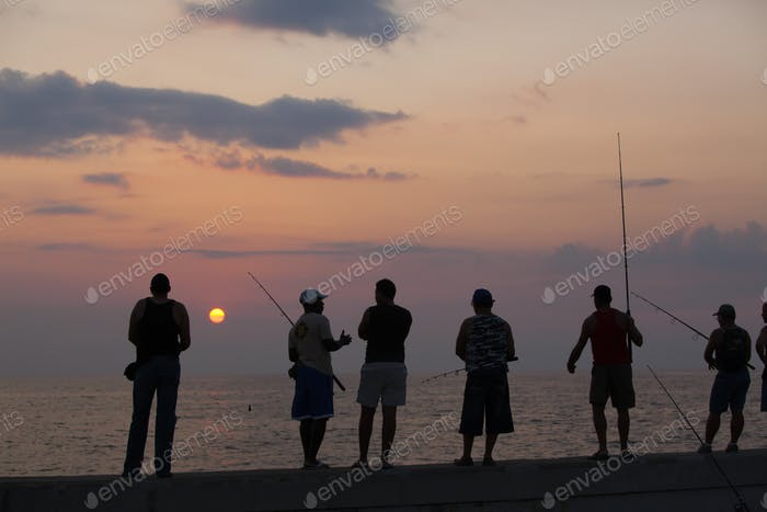 Fishermen trying their luck, standing on the railing of the Malecon in Havana, Cuba