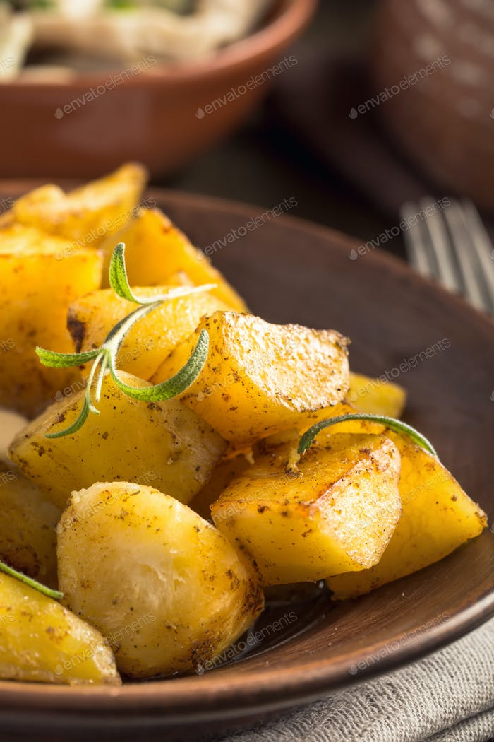 Baked potato with rosemary on plate vertical