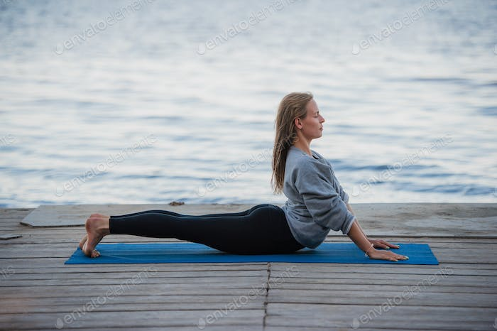 Young sport woman practicing yoga on the beach