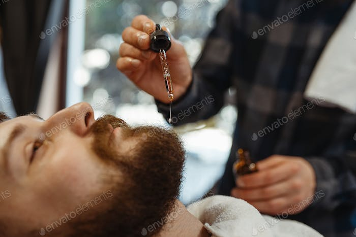Barber and customer, beard cutting closeup