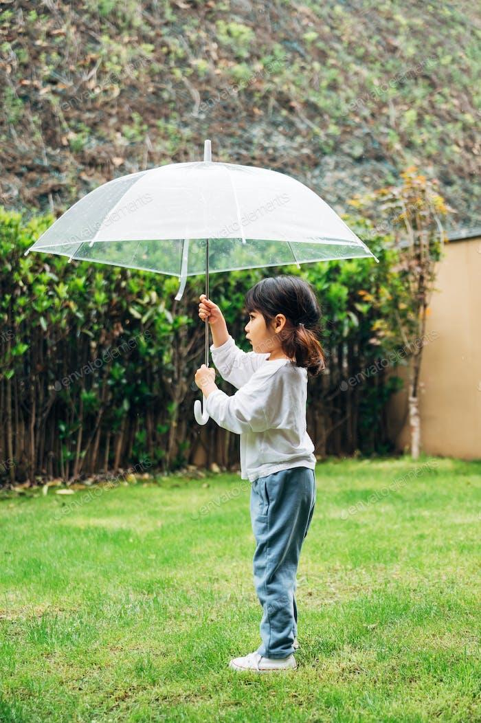 Cute little girl holding umbrella on the grass