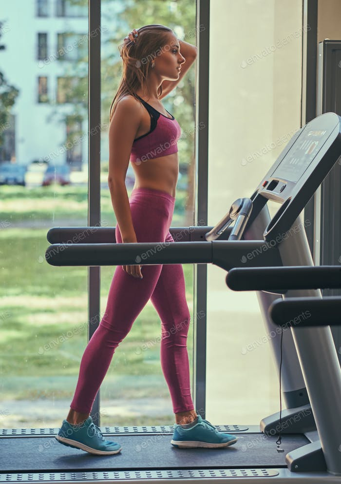 Side view of a young sportswoman in a pink sportswear, training on the treadmill at a gym.