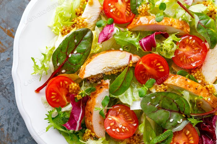 Fresh vegetable salad with grilled chicken meat, top view